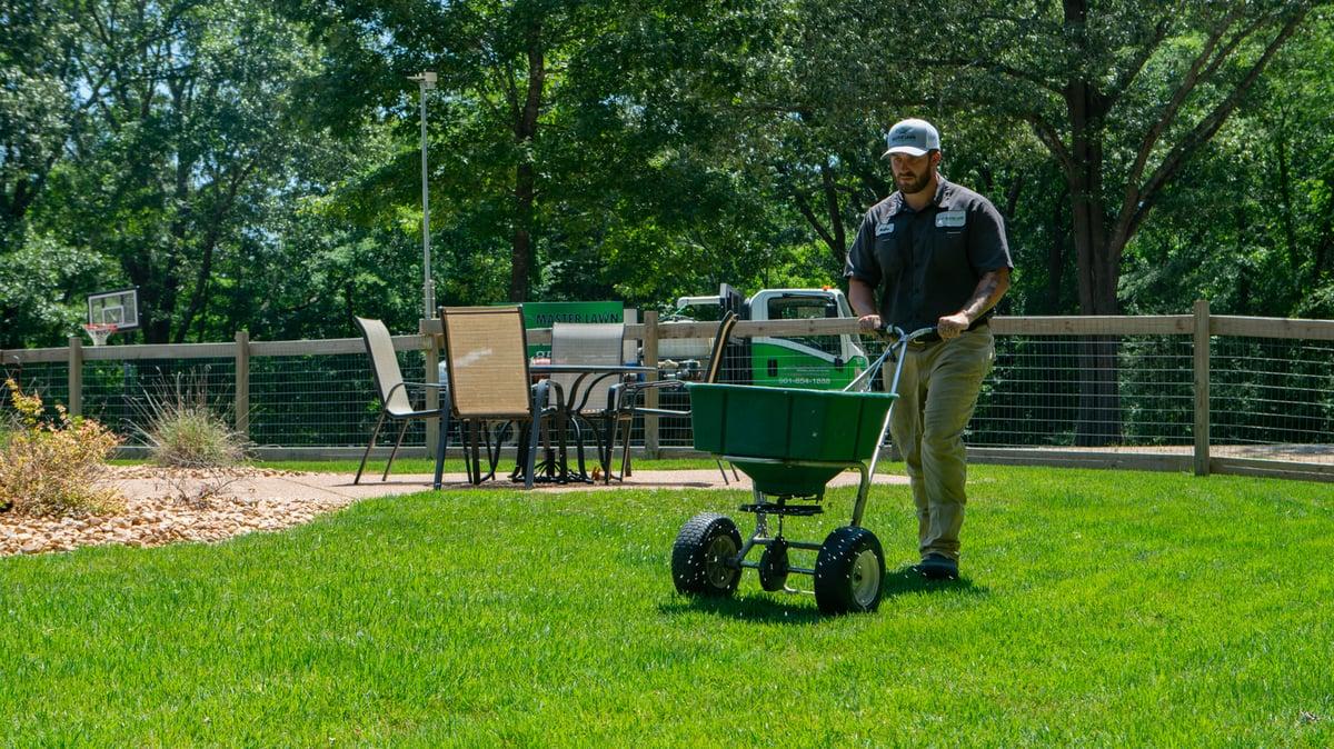 landscape professional fertilizing lawn using granular fertilizer