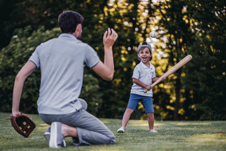 dad and son playing baseball on nice grass