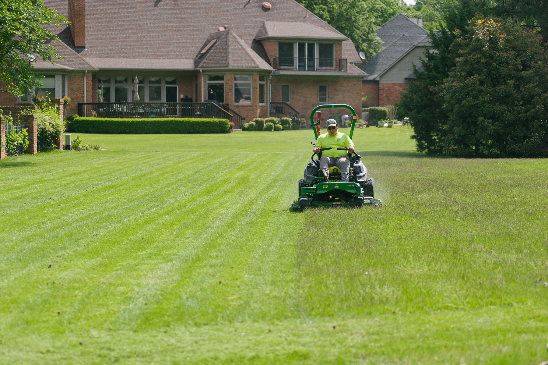 Professional lawn care technician mowing lawn