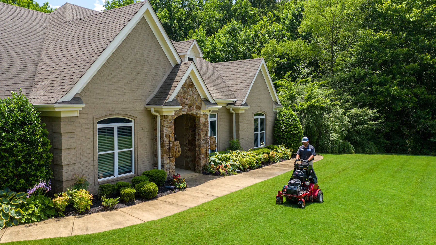 lawn care technician aerating a lawn