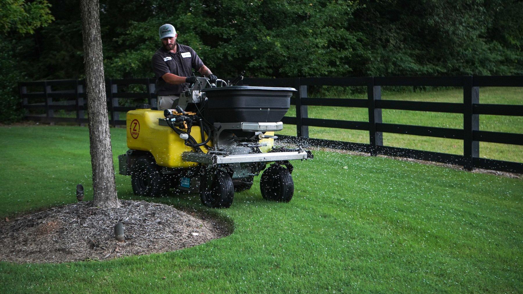 lawn care technician applying granular fertilizer