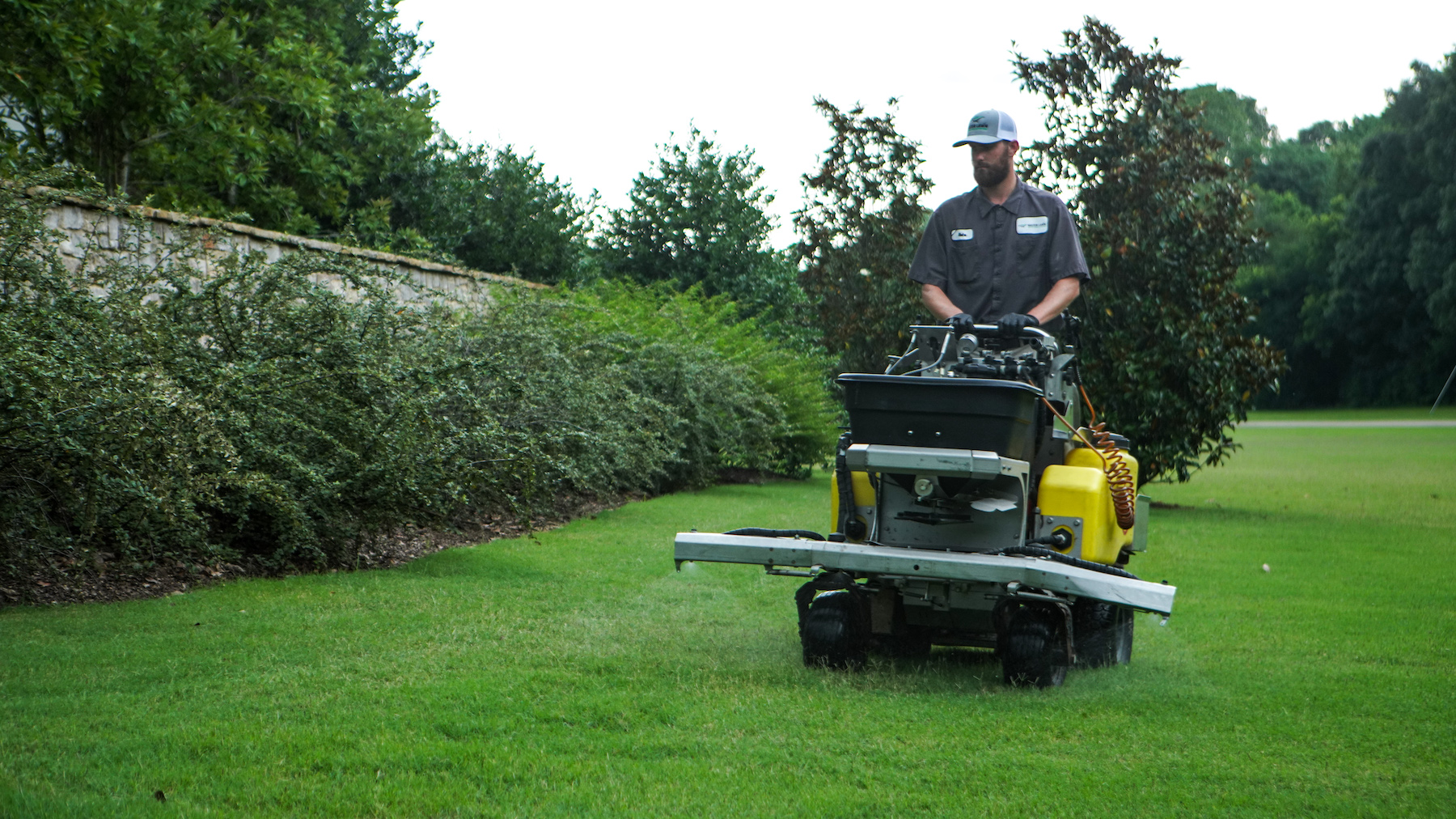 lawn care technician spraying with ride on sprayer