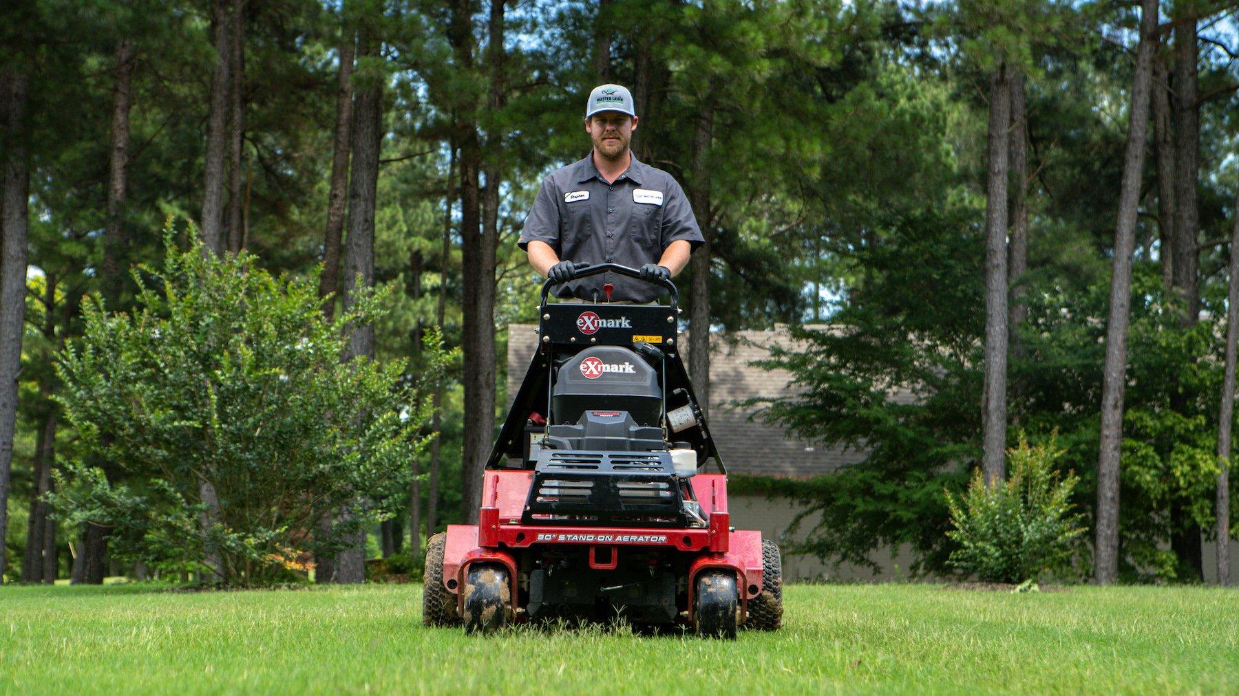 Lawn care technician using an aerator