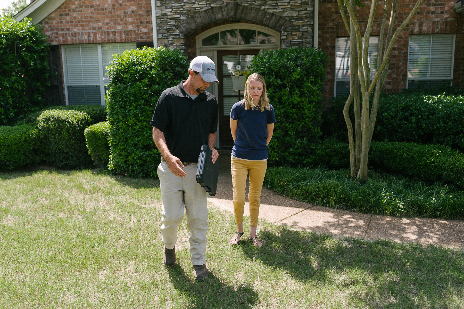 Master Lawn care technician identifying grass with customer