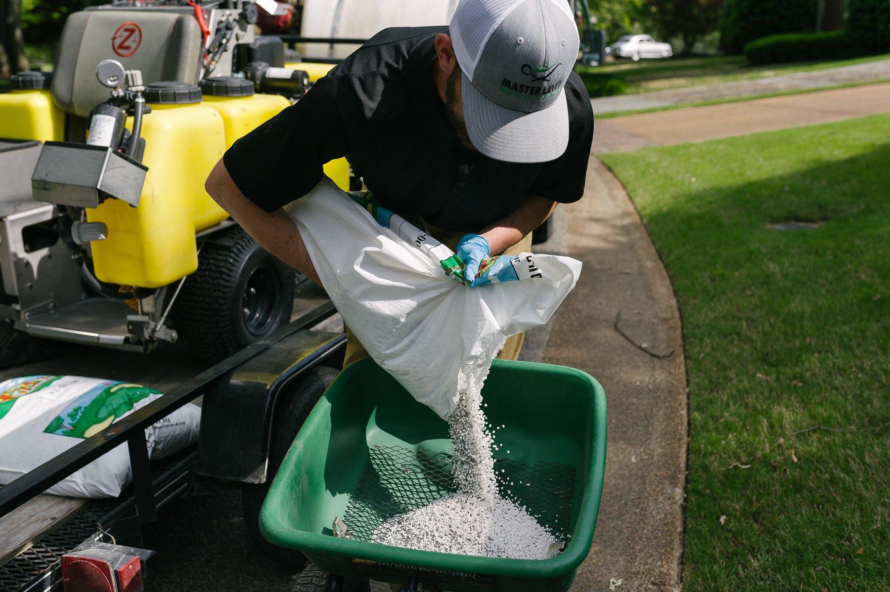 landscape technician pouring granular fertilizer