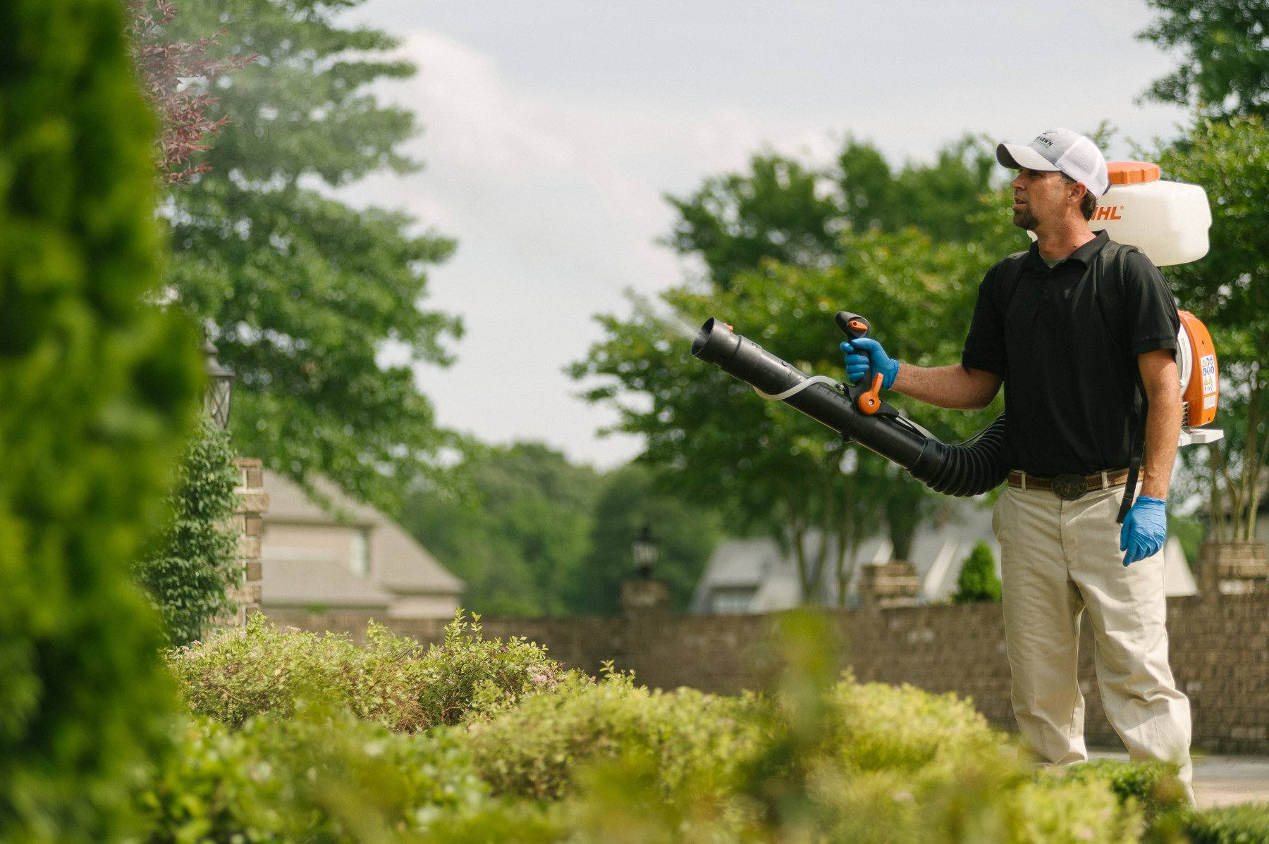 mosquito control technician spraying shrubs