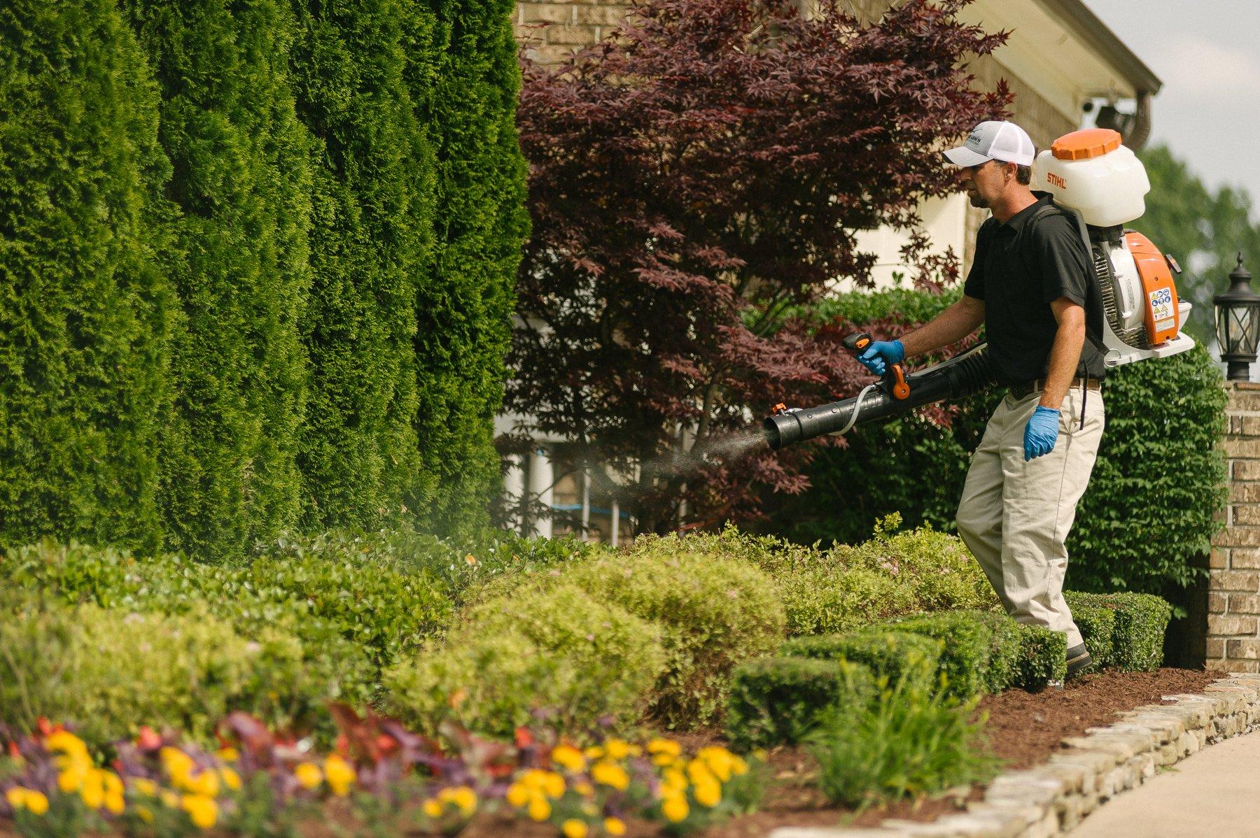 technician spraying organic mosquito spray