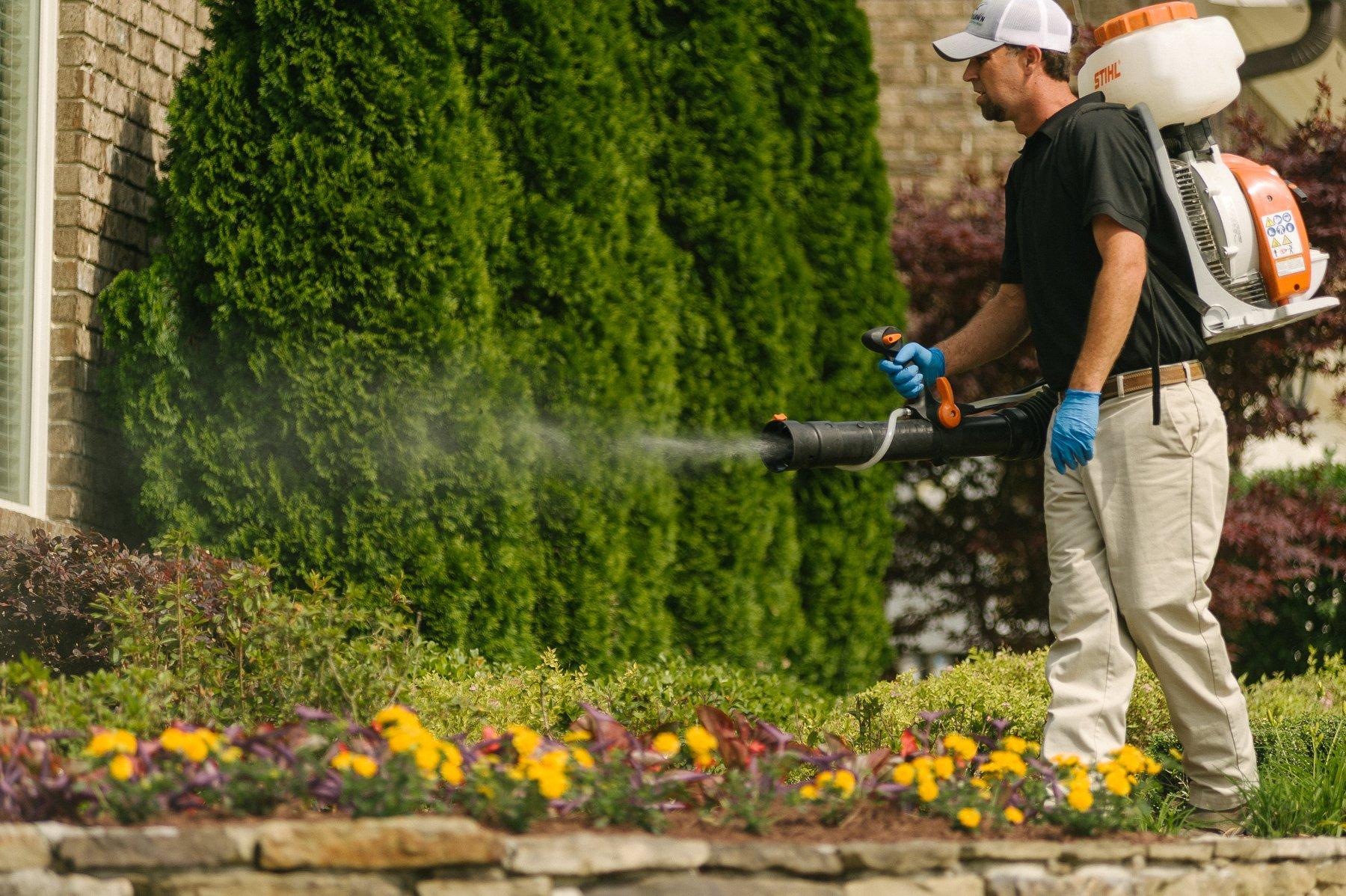 Technician spraying mosquito control