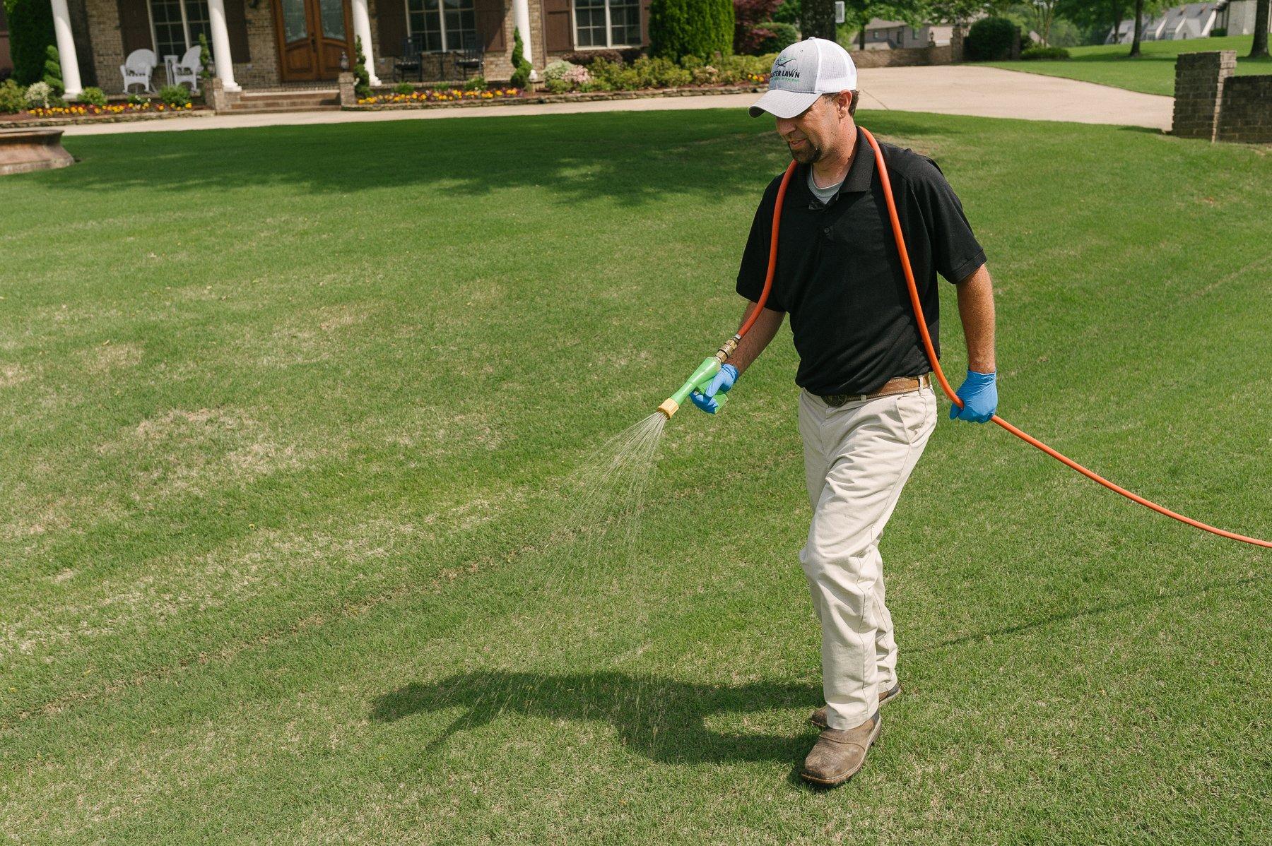 lawn care technician applying crabgrass preventer