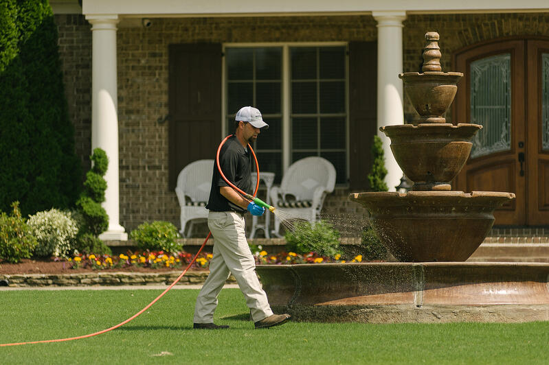 technician-spraying-lawn-hose-9
