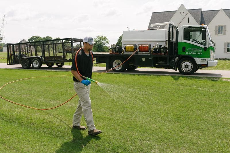 technician-spraying-lawn-hose-truck-3