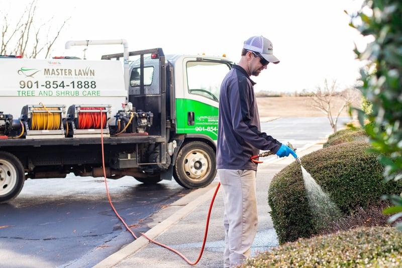 plant health care technician fertilizing shrubs