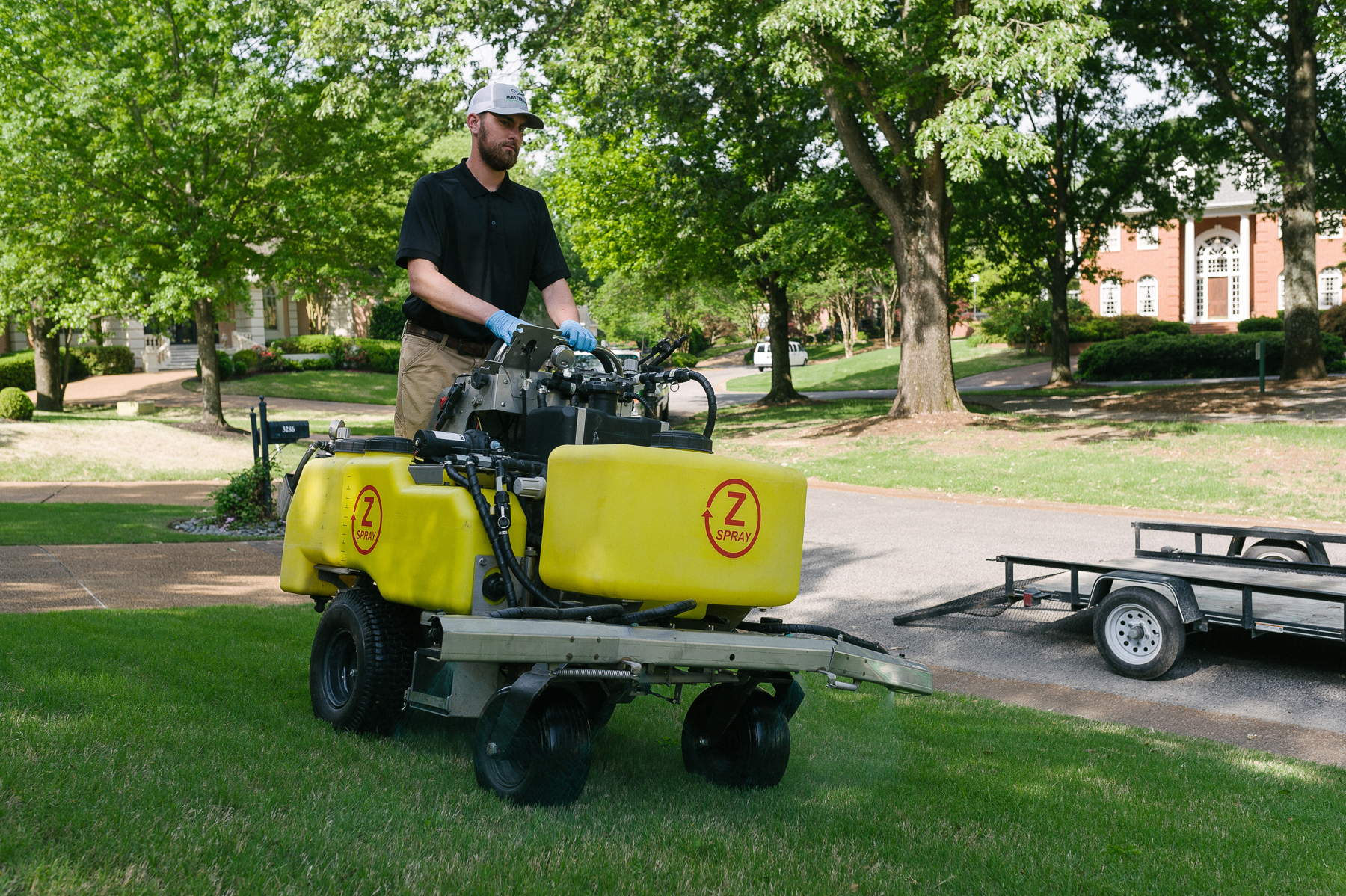 Lawn care technician using a ride-on machine sprayer