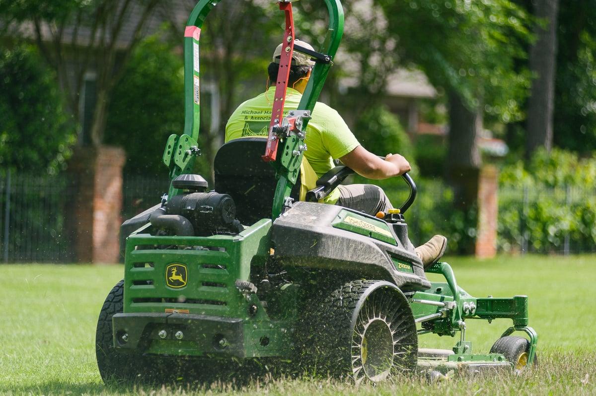 lawn technician mowing lawn in fall